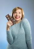 Femme heureuse d'intoxiqué de chocolat jugeant la grande bouche de barre expression enthousiaste souillée et folle de visage photographie stock libre de droits