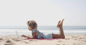 Femme heureuse dactylographiant sur un ordinateur portable sur une plage photos stock