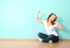 Femme heureuse dans des écouteurs écoutant la musique dans une chambre avec un b Images stock
