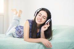 Femme heureuse dans des écouteurs avec les yeux fermés photos stock