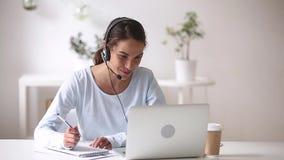 Femme heureuse dans des écouteurs parlant par le webcam faisant des notes clips vidéos