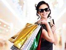 Femme heureuse dans des lunettes de soleil avec l'achat. Image stock