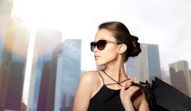 Femme heureuse dans des lunettes de soleil noires avec des paniers image stock