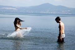 Femme heureuse dans l'amour éclaboussant l'ami dans l'eau dans les vacances en Italie Image libre de droits