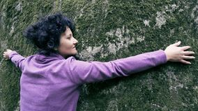 Femme heureuse dans l'amour détendant étreignant une pierre énorme avec de la mousse Image libre de droits