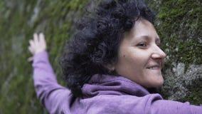 Femme heureuse dans l'amour détendant étreignant une pierre énorme avec de la mousse dans la forêt Images stock