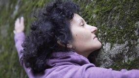 Femme heureuse dans l'amour détendant étreignant une pierre énorme avec de la mousse dans la forêt Photographie stock
