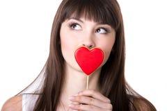 Femme heureuse dans l'amour tenant le biscuit en forme de coeur Photos stock