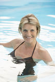 Femme heureuse dans la natation de vêtements de bain dans la piscine Image libre de droits