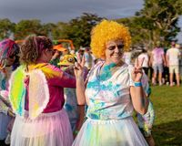 Femme heureuse dans la perruque orange à la course d'amusement de frénésie de couleur images stock