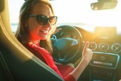 Femme heureuse dans la robe rouge avec le pouce se reposant dans la voiture photos stock