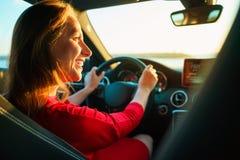 Femme heureuse dans la robe rouge conduisant la voiture image libre de droits