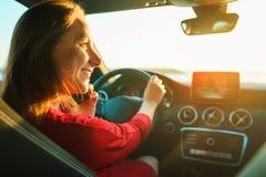 Femme heureuse dans la robe rouge conduisant la voiture photographie stock