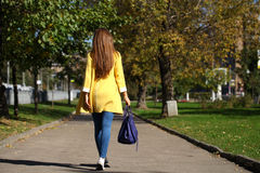 Femme heureuse dans la rue de marche d'automne de manteau jaune Photos stock