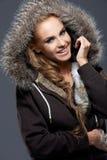 Femme heureuse dans la veste avec le capot velu Image libre de droits