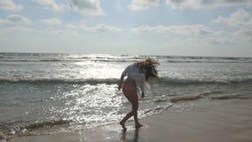 Femme heureuse dans le bikini et la chemise marchant sur l'eau à la plage près de l'océan Jeune belle fille appréciant la vie et banque de vidéos