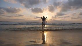 Femme heureuse dans le bikini et la chemise marchant sur la plage près de l'océan et appréciant des vacances Jeune belle rotation banque de vidéos
