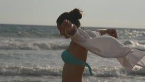 Femme heureuse dans le bikini et la chemise marchant sur la plage près de l'océan et de la main augmentée Jeune belle fille appré banque de vidéos