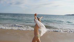 Femme heureuse dans le bikini et la chemise marchant sur la plage près de l'océan et soulevant la main Jeune belle fille apprécia banque de vidéos