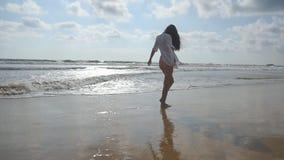 Femme heureuse dans le bikini et la chemise marchant sur la plage près de l'océan Jeune belle fille appréciant la vie et ayant l' banque de vidéos