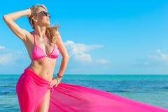 Femme heureuse dans le bikini rose couvert de morceau de tissu Photographie stock libre de droits