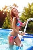 Femme heureuse dans le bikini s'élevant dans la piscine image stock