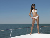 Femme heureuse dans le bikini se tenant sur l'arc du yacht photo stock