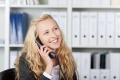 Femme heureuse dans le bureau parlant au téléphone Photo libre de droits