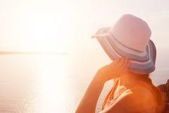 Femme heureuse dans le chapeau du soleil appréciant la vue de mer Santorini, Grèce Images libres de droits
