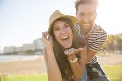 Femme heureuse dans le chapeau riant avec son ami dehors Photographie stock libre de droits