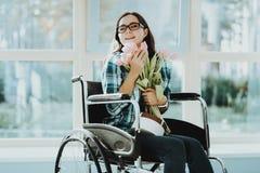 Femme heureuse dans le fauteuil roulant avec des fleurs à l'aéroport photographie stock libre de droits