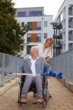 Femme heureuse dans le fauteuil roulant sur un rampe Photographie stock libre de droits