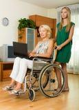 Femme heureuse dans le fauteuil roulant travaillant sur l'ordinateur portable Image stock