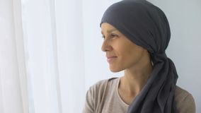 Femme heureuse dans le foulard regardant dans la fenêtre, rétablissement après le traitement contre le cancer banque de vidéos
