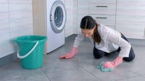 Femme heureuse dans le plancher en caoutchouc rose de cuisine de lavages de gants avec un tissu Tuiles grises sur le plancher clips vidéos