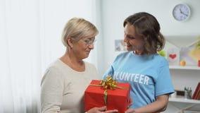 Femme heureuse dans le T-shirt volontaire donnant le boîte-cadeau à la dame âgée, charité de vacances banque de vidéos