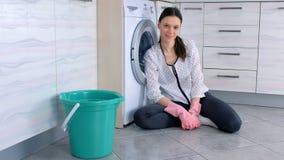 Femme heureuse dans les gants en caoutchouc roses dans le plancher de cuisine après nettoyage des regards à la caméra banque de vidéos