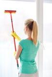 Femme heureuse dans les gants nettoyant la fenêtre avec l'éponge Image stock
