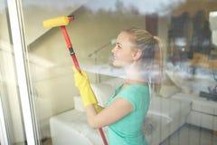 Femme heureuse dans les gants nettoyant la fenêtre avec l'éponge photographie stock libre de droits