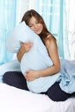 Femme heureuse dans son lit avec un oreiller Photos libres de droits