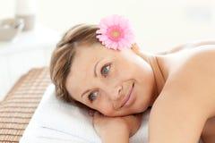 Femme heureuse dans une station thermale avec une fleur Image stock