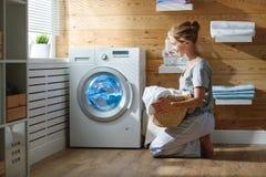 Femme heureuse de femme au foyer dans la buanderie avec la machine à laver Photo libre de droits
