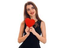 Femme heureuse de brune dans l'amour posant avec le coeur rouge dans des ses mains d'isolement sur le fond blanc Image stock
