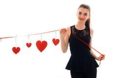 Femme heureuse de brune dans l'amour posant avec le coeur rouge sur le fond d'isolement sur le fond blanc Photographie stock