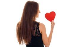 Femme heureuse de brune dans l'amour posant du postérieur avec le coeur rouge dans des ses mains d'isolement sur le fond blanc Images stock