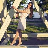 Femme heureuse de brune dans un amusement de détente de robe en parc se penchant sur les piles en bois dans l'apprécier vos vacan Image stock