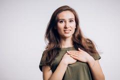 Femme heureuse de brune tenant le coeur de mains et souriant sur le fond blanc Émotion, joie photo stock