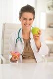 Femme heureuse de docteur donnant la pomme au lieu du beignet Image libre de droits