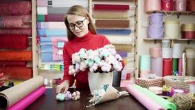 Femme heureuse de fleuriste dans un pullover rouge enveloppant des fleurs en papier au fleuriste Elle essaye de composer les fleu banque de vidéos