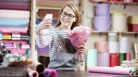 Femme heureuse de fleuriste enveloppant des fleurs en papier au fleuriste Elle prend une photo des fleurs Elle essaye de composer clips vidéos